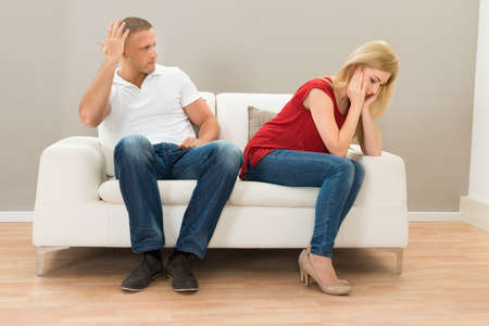 Depressed Young Couple Sitting On Sofa At Home photo