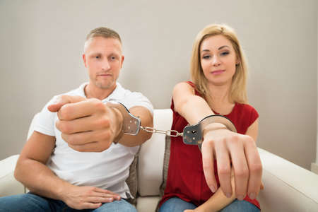 woman handcuffs: Portrait Of Unhappy Young Couple Handcuffed Together Stock Photo
