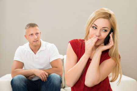 hark: Wife Talking Privately On Mobile Phone While Husband Sitting On Sofa
