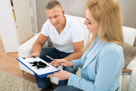 psychologist: Patient Looking At Rorschach Inkblot Held By Female Psychologist Stock Photo