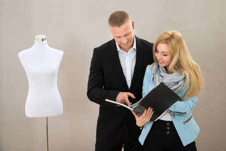 alterations: Young Female Tailor With Male Client Looking At Catalogue In Store