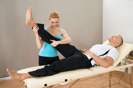 Young Female Instructor Helping Man For Doing Exercising Stock Photo