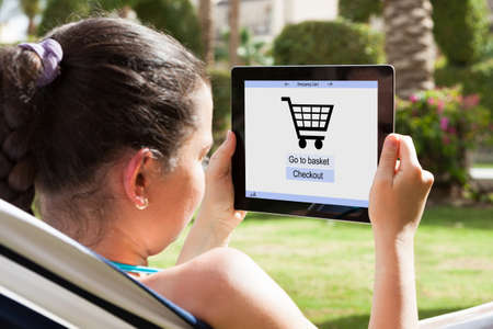 Close-up Of Young Woman Shopping Online With Digital Tablet photo