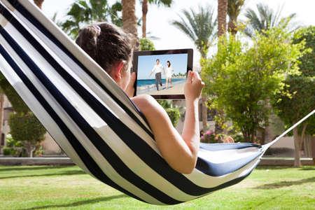 Mujer joven tumbado en la hamaca Vídeo Visualización En Tableta digital Foto de archivo