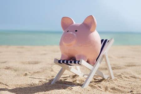 Piggy Bank With Deckchair On Sandy Beach Imagens
