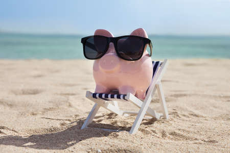 Piggy Bank On Deckchair With Sunglasses Reklamní fotografie - 38473329