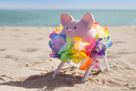 Piggy Bank With Colorful Garland On Beach photo