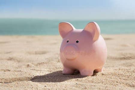 Photo Of Pink Piggy Bank On Sandy Beach Imagens