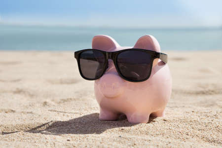 bank accounts: Pink Piggy Bank With Black Sunglasses On Beach