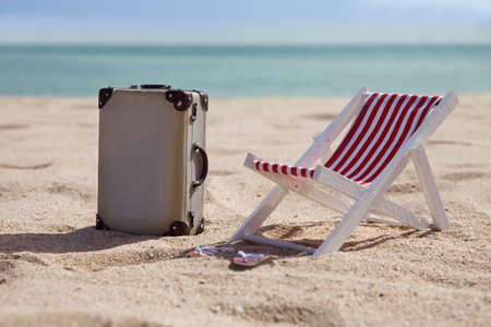 deck chairs: Miniature Deckchair With Suitcase On Sandy Beach