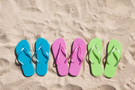 thong: Three Pairs Of Flip-flops In A Row On Beach