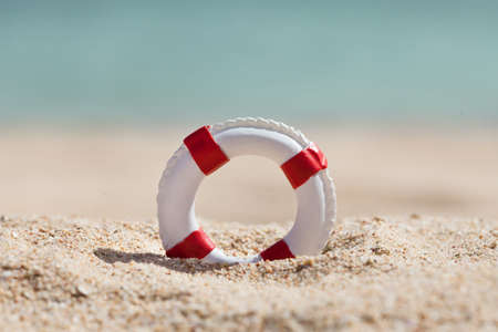 insurance protection: Close-up Of Miniature Lifebuoy On Sandy Beach