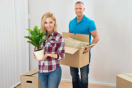 relocating: Portrait Of Happy Young Couple Moving Boxes In New Home Stock Photo