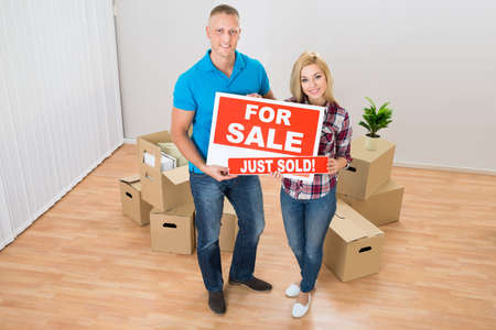 selling house: Happy Couple Holding Sold Sign In Their New Home