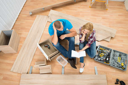 Portrait Of Thoughtful Couple With Disassembled Furniture Parts In New Home Stock Photo