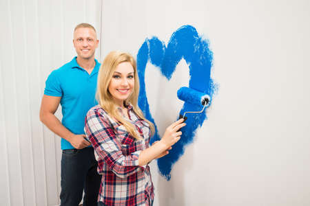 Portrait Of Young Couple Painting Heart On Wall With Blue Paint photo