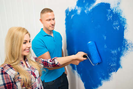 Portrait Of Happy Young Couple Painting Wall With Paint Roller photo