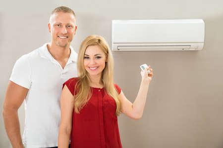 Portrait Of Happy Couple Holding Remote Control Air Conditioner Stock Photo