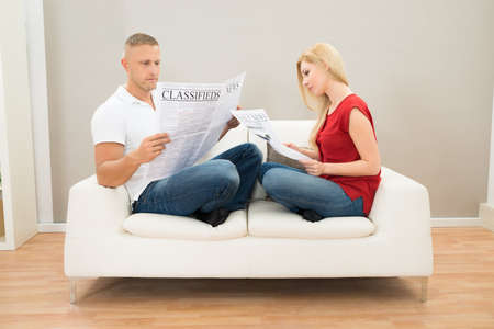 Young Couple Sitting On Sofa Reading Newspapers photo
