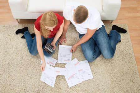 Vysoký úhel pohledu Mladý pár výpočtu účty s kalkulačkou doma