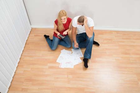 planificación familiar: Opinión de alto ángulo de la joven pareja sentada en el suelo Cálculo Bills
