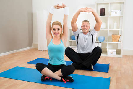 core: Portrait Of Young Couple Exercising Sitting On Mat