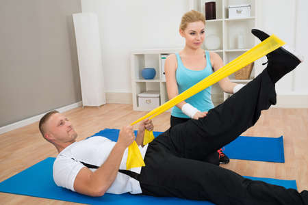Female Instructor Helping Young Man While Exercising On Blue Exercise Mat photo