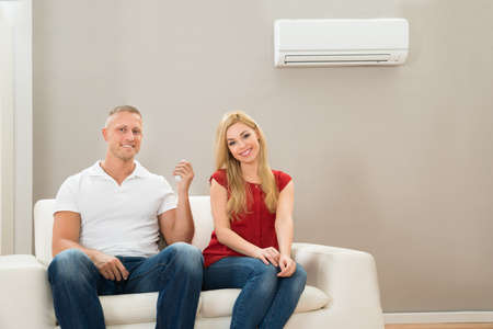 room air: Young Happy Couple Sitting On Sofa Using Air Conditioner Stock Photo