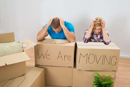 family moving house: Frustrated Young Couple With Moving Boxes At Home