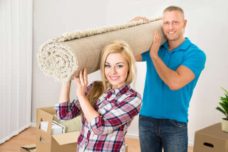 man carrying box: Happy Young Couple Carrying Rolled Carpet In Their New Home