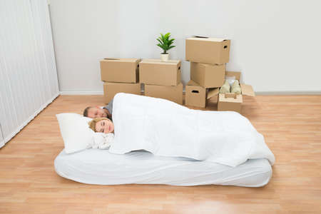 mattress: Young Couple Sleeping On Mattress In New Home