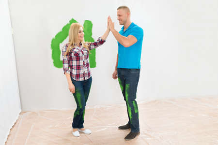 Happy Couple Giving High Five To Each Other In Front Home Painted Wall photo