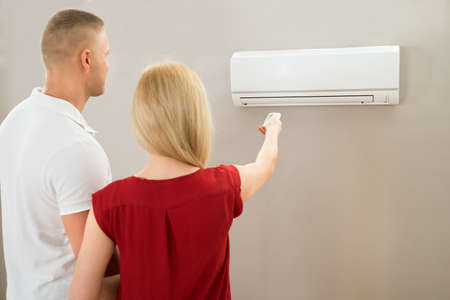 room air: Young Couple Adjusting Temperature With Remote Control Of Air Conditioner Stock Photo