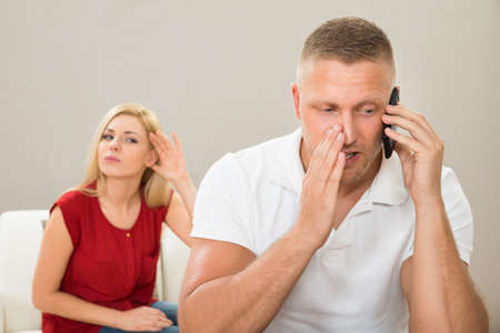 hark: Wife With Curiosity Looking At Husband Talking Privately On Mobile Phone