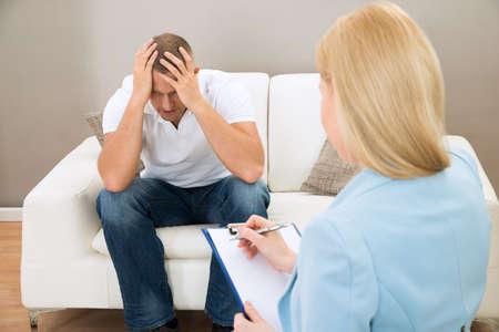 terapia psicologica: Paciente deprimida que se sienta en el sofá delante de la psiquiatra que toma notas