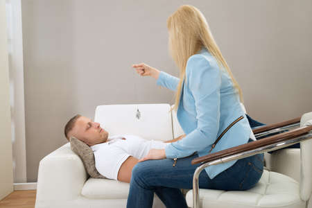 hypnotherapy: Female Psychiatrist Hypnotizing Patient Lying On Couch