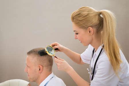 piojos: Primer plano Mujer dermatólogo Mirando a pelo del paciente a través de la lupa