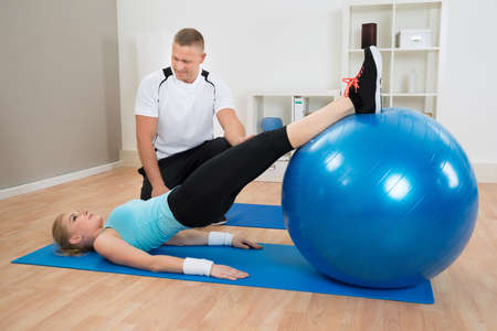 exerting: Male Instructor Looking At Woman Exerting With Pilate Ball