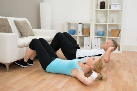 fitness workout: Young Couple Doing Workout Together At Home Stock Photo