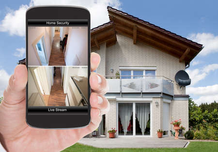 monitoring system: Close-up Of Person Hand Holding Mobile Phone With Home Security System