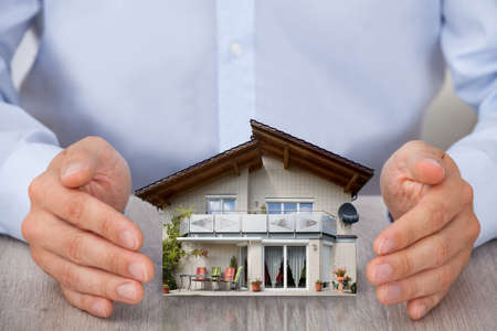 to trust: Close-up Of Man Saving Small House Model