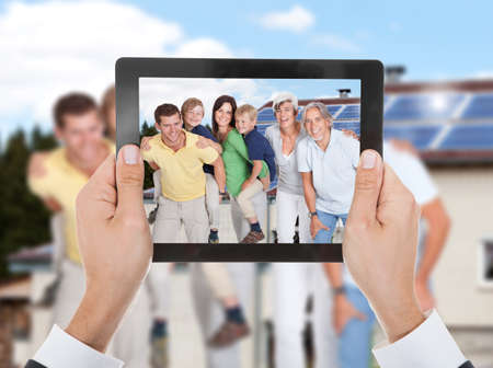 two generation family: Close-up Of Hand Taking Photo Of Two Generation Family With Digital Tablet Stock Photo