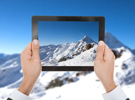 taking photograph: Close-up Of Person Hand Taking Photo Of Snowy Mountain Stock Photo