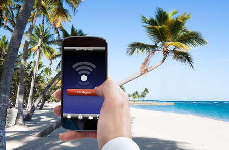 ビーチでの携帯電話の Wifi 信号がないと人の手のクローズ アップ