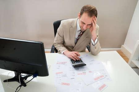 unpaid: Portrait Of Worried Businessman Calculating Unpaid Bills At Desk