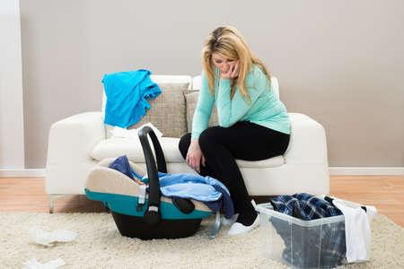 agotado: Madre infeliz con ropa de lavandería y el bebé en la cuna