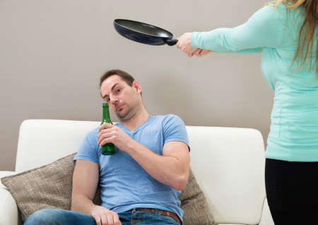 beating: Wife Hitting With Pan To Lazy Husband Sitting On Sofa