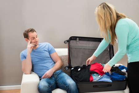 mujer con maleta: Hombre sentado al lado La maleta mientras que la mujer de ropa plegable