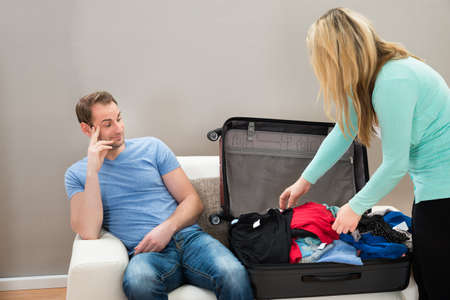 bored man: Man Sitting Beside The Suitcase While Woman Folding Clothes