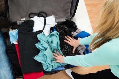 femme valise: Vue en plongée Of Woman emballage des vêtements Dans Suitcase